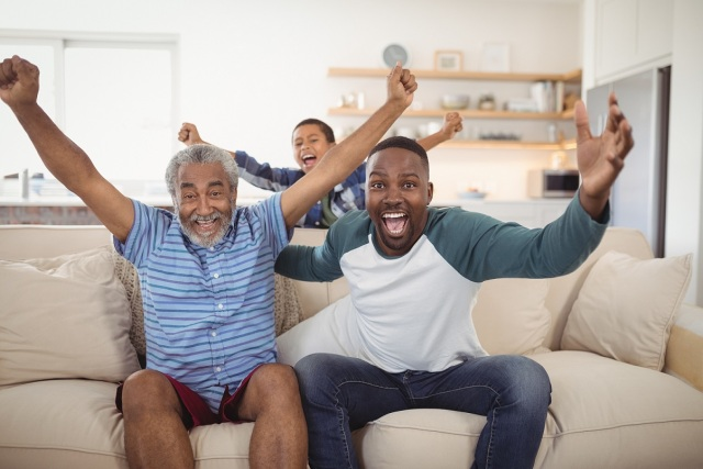 Family cheering while watching television in living room